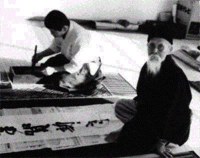 January 3rd, 1969. The Founder writes brush calligraphy on the second floor of Hombu dojo. The person making the ink is Mr. Kaneko. At the top right hand side of the photo is the Founder's futon where he slept